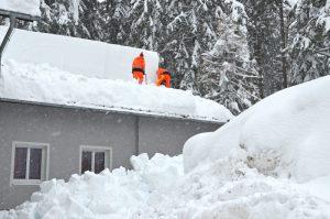 Arbeiter befreien Dach von Schnee